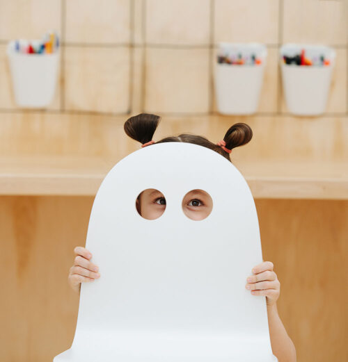 Funny moment a child plays, eyes in the holes of a chair and peeping pigtails. High quality photo